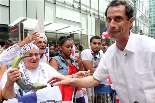 Anthony Weiner, running in the New York Mayors race, right, reacts after sharing a moment with a spectator and her plantains, left, as he takes part in the Dominican Day Parade on New York's Avenue of the Americas Sunday Aug. 11, 2013.