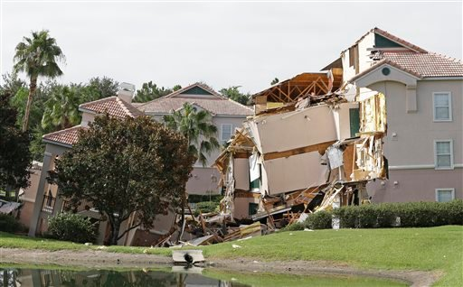 Damage to buildings caused by a sinkhole 40 to 50 in diameter is seen at the Summer Bay Resort, Monday, Aug. 12, 2013, in Clermont, Fla. (AP)