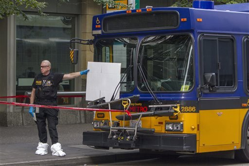 A police investigator holds a white card up to the bus window where a Metro driver was shot, on 3rd and Union in Seattle, Wash., Monday Aug. 12, 2013. (AP)