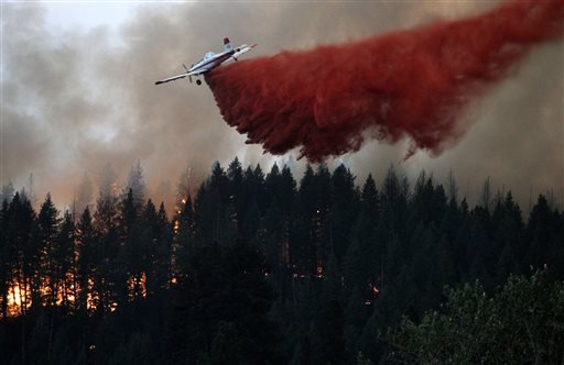An air tanker drops fire retardant on the hillside overlooking Pine, Idaho while battling the more than 80,000 acres Elk Complex FIre on Sunday Aug.11, 2013. (AP Photo/Times-News,Ashley Smith)
