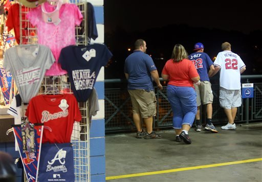 Baseball fans look over a railing at Turner Field near the scene where a man fell 60 feet from the upper deck Monday Aug. 12, 2013.