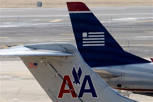 In this Thursday, Feb. 14, 2013, file photo, American Airlines and US Airways jets prepare for flight at a gate at the Philadelphia International Airport in Philadelphia.