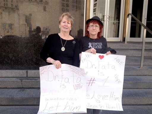 Sally Kelly, 70, left, of Lake Orion, Mich. and Theresa Pickering, 48, of Dryden, Mich., both cancer patients of Dr. Farid Fata, hold signs outside Federal Court in Detroit on Tuesday, Aug. 13, 2013 in support of the Oakland Township oncologist. (AP)