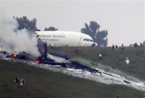 Debris burns as a UPS cargo plane lies on a hill at Birmingham-Shuttlesworth International Airport after crashing on approach, Wednesday, Aug. 14, 2013, in Birmingham, Ala. (AP Photo/Hal Yeager)