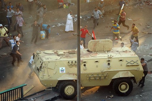 Supporters of ousted Islamist President Mohammed Morsi capture an Egyptian security forces vehicle at the Ministry of Finance in Cairo, Egypt, Wednesday, Aug. 14, 2013. (AP)