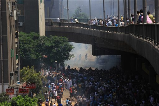 Supporters of Egypt's ousted President Mohammed Morsi clash with security forces near the largest sit-in by supporters of Morsi in the eastern Nasr City district of Cairo, Egypt, Wednesday, Aug. 14, 2013. (AP)
