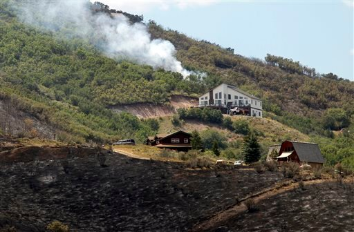 A hot spot flares up above homes in Rockport Estates in Wanship, Utah, Wednesday, Aug. 14, 2013. (AP Photo/The Salt Lake Tribune, Al Hartmann)