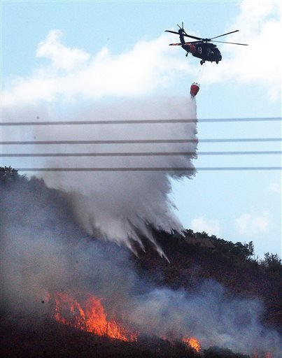 A helicopter drops water near a home at the Rockport fire in Rockport, Summit County, Utah, Wednesday, Aug. 14, 2013. (AP Photo/The Deseret News, Ravell Call)