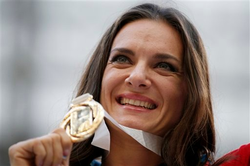 Russia's Yelena Isinbayeva poses with her gold medal in the women's pole vault as she stands on the podium during the medal ceremony at the World Athletics Championships in the Luzhniki stadium in Moscow, Russia, Thursday, Aug. 15, 2013.