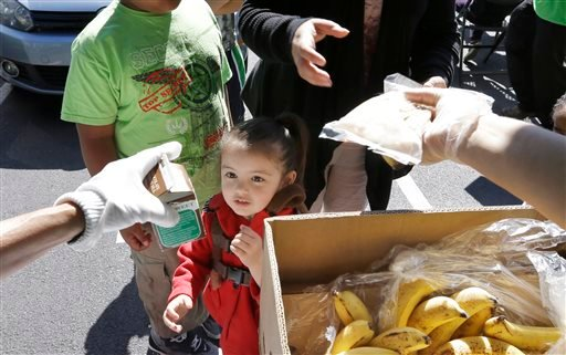 In this photo taken July 15, 2013, a child looks at the carton of milk she's being handed during a lunch program in Federal Way, Wash.