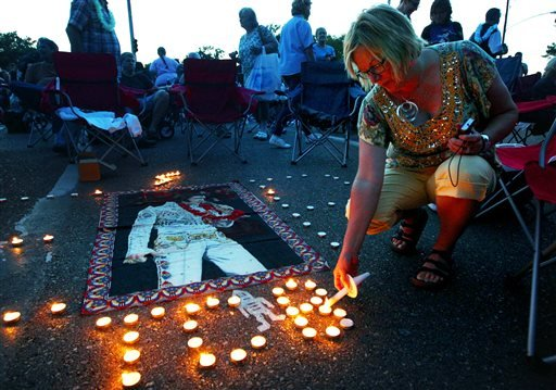 Elvis Presley fan Jill Gibson lights candles outside Graceland, Presley's home, before the annual candlelight vigil on Thursday, Aug. 15, 2013, in Memphis, Tenn. (AP)