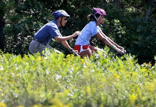 President Barack Obama and daughter Malia ride bicycles in Manuel F. Correllus State Forest in West Tisbury, Mass., Friday, Aug. 16, 2013.