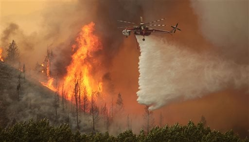 Helicopters battle the 64,000 acre Beaver Creek Fire on Friday, Aug., 16, 2013 north of Hailey, Idaho. A number of residential neighborhoods have been evacuated because of the blaze.(AP Photo/Times-News, Ashley Smith)