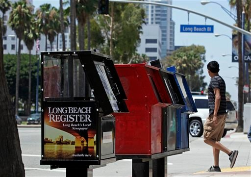 This Aug. 15, 2013, photo shows new, empty news stands ready to hold copies of the Long Beach Register on Ocean Boulevard in Long Beach, Calif.