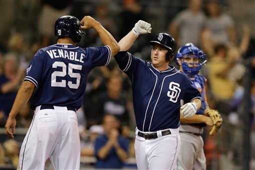 San Diego Padres' Jedd Gyorko, center, bumps elbows with teammate Will Venable, left, after hitting a three-run home run as New York Mets catcher Travis d'Arnaud looks on at right during the eighth inning in a baseball game Saturday, Aug. 17, 2013.