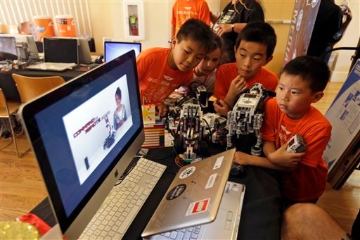In this Aug. 14, 2013, photo, children look at a computer presentation on how to assemble Lego parts during a Digital Media Academy workshop in Stanford, Calif.