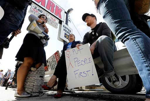 In this July 24, 2013, file photo, protesters sit across the street from the federal courthouse in Detroit after a judge stopped any lawsuits challenging the city's bankruptcy.