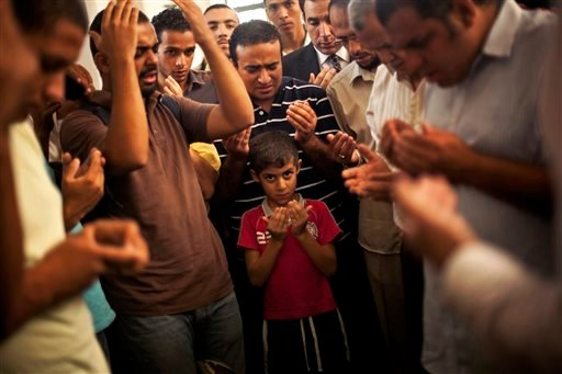 A son of the late Ammar Badie prays during his father's funeral in al-Hamed mosque in Cairo's Katameya district on Sunday, Aug. 18, 2013.