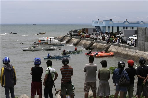 A crowd watches as divers continue their search and rescue operation off Talisay coast, Cebu province Sunday, Aug. 18, 2013 following Friday night's collision of the passenger ferry MV Thomas Aquinas and the cargo ship MV Sulpicio Express Siete.