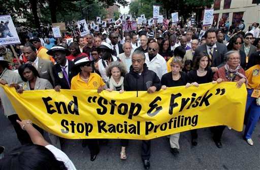"""In this June 17, 2012, file photo, the Rev. Al Sharpton, center, walks with demonstrators during a silent march to end New York's """"stop-and-frisk"""" program."""