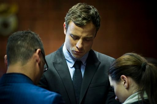 Oscar Pistorius cries as he prays with his sister Aimee and brother Carl in the magistrates court in Pretoria, South Africa, Monday, Aug. 19, 2013.