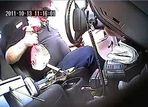 In this Oct. 13, 2011 image taken from surveillance video and released by the U.S. Attorney's Office for the Northern District of New York, former parking meter mechanic James Bagarozzo lifts a bag of quarters off the the seat of a truck.