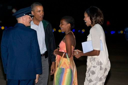President Barack Obama, second from left, Sasha Obama, and first lady Michelle Obama, are greeted as they exit Air Force One on arrival at Andrews Air Force Base, Md., on Sunday Aug. 18, 2013, after a family vacation on the island of Martha's Vineyard.