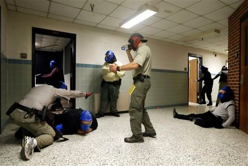 FBI instructor Mike Sotka, center, films local police officers as they participate in an active shooter drill in a college classroom building in Salisbury, Md.