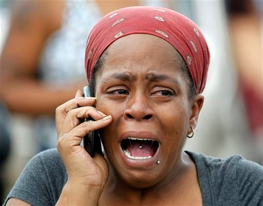 Nicole Webb cries as she talks on a phone in the parking lot of a store while waiting for her 9-year-old son, a student at Ronald E. McNair Discovery Learning Academy in Decatur, Ga., on Tuesday, Aug. 20, 2013.