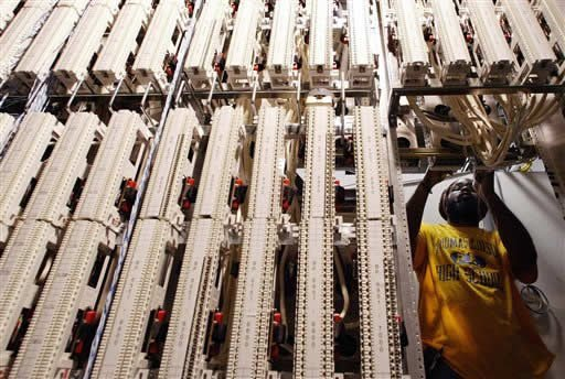 FILE - In this Thursday, Aug. 26, 2004, file photo, Verizon special service technician Mark Rose adjust cables attached to a framework in a Verizon network room at the Main Post Office in New York. (AP)