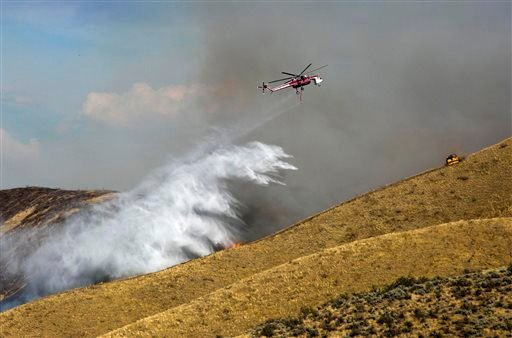 A fire attack helicopter drops water along a draw northeast of Hilltop Cafe on Idaho 21 as a bulldozer plows a fire line on the ridge Tuesday Aug. 20, 2013 northeast of Boise. (AP Photo/The Idaho Statesman, Darin Oswald)