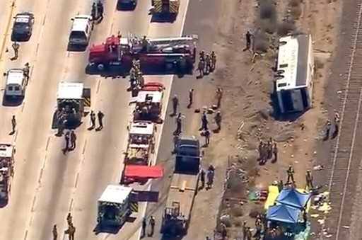 This video image provided by KABC-TV shows rescue officials working the scene of an accident where a tour bus, left, crashed and turned over injuring multiple passengers Thursday Aug. 22, 2013 in Los Angeles. (AP)