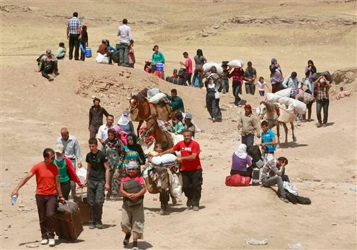 Syrian refugees cross into Iraq at the Peshkhabour border point in Dahuk, 260 miles (430 kilometers) northwest of Baghdad, Iraq, Tuesday, Aug. 20, 2013.