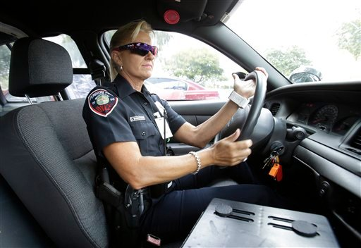 In this photo taken Thursday, Aug. 22, 2013, Dara Van Antwerp, the school resource officer at Panther Run Elementary School, drives her patrol car in Pembroke Pines, Fla., in the suburbs of Fort Lauderdale.