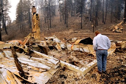 U.S. Sen. Jon Tester, D-Mont., looks at the remains of a Lolo Creek home that was destroyed by the West Fork II fire when it swept down the Lolo Creek canyon, Wednesday, Aug. 21, 2013 near Lolo, Mont.