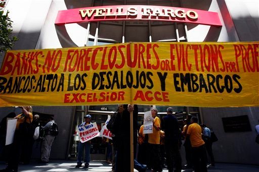 In this Thursday, Aug. 15, 2013 photo, protesters hold a banner outside of Wells Fargo headquarters in San Francisco.