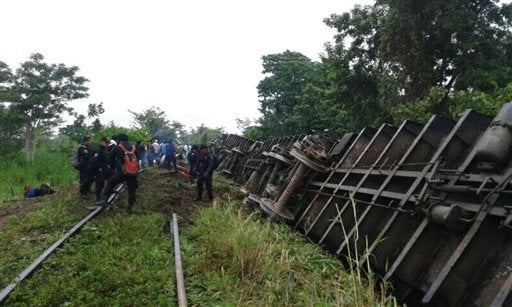 In this photo release by the Civil Protection of the State of Tabasco, police agents work at a site where a train derailed in Tabasco, Mexico, Sunday, Aug. 25, 2013.