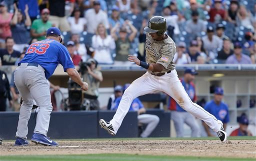 San Diego Padres' Ronny Cedeno scores as Chicago Cubs relief pitcher Kevin Gregg searches for the ball in the thirteenth inning of a baseball game Sunday, Aug. 25, 2013, in San Diego. Cedeno scored from third on a wild pitch. (AP Photo/Lenny Ignelzi)