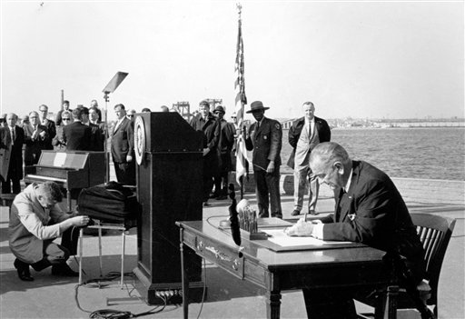 In this Oct. 3, 1965, file photo U.S. President Lyndon B. Johnson sits at his desk on Liberty Island in New York Harbor as he signs a new immigration bill.