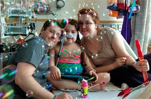 In this May 30, 2013 file photo provided by the Murnaghan family, Sarah Murnaghan, center, celebrates the 100th day of her stay in Children's Hospital of Philadelphia with her father, Fran, left, and mother, Janet.