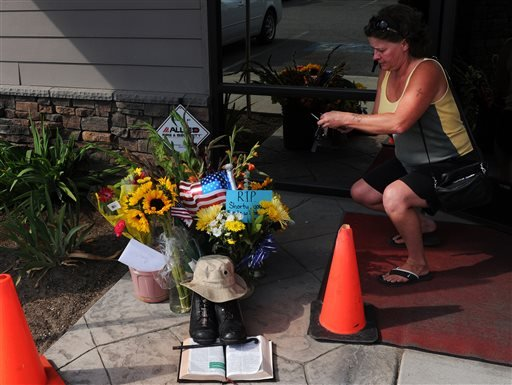 In this Aug. 22, 2013, photo, Lill Duncan takes a photo of a memorial for Delbert Belton, an 88-year-old World War II veteran who was beaten to death, in Spokane, Wash.