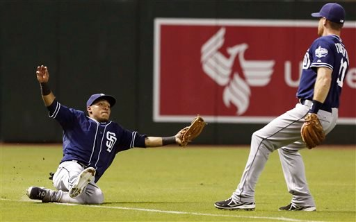San Diego Padres' Alexi Amarista, left, makes a sliding catch on a ball hit by Arizona Diamondbacks' Eric Chavez as Logan Forsythe looks on during the fourth inning of a baseball game on Monday, Aug. 26, 2013, in Phoenix. (AP Photo/Ross D. Franklin)