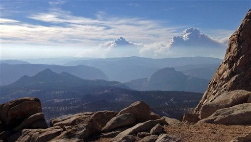 Smoke clouds and bands of haze from the Rim Fire in the western Sierra Nevada loom up some 20 miles behind the famed granite monolith known as Half Dome, right center, seen from 11,500-foot Mt. Clark in Yosemite Valley in Yosemite National Park, Calif.