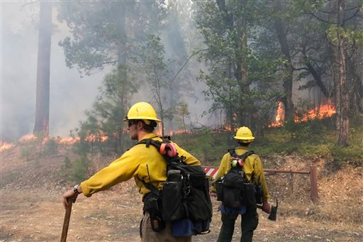Two firefighters watch trees burn while battling the Rim Fire near Yosemite National Park, Calif., on Monday, Aug. 26, 2013.