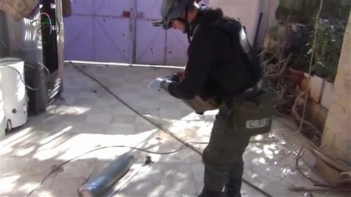 In this image taken from amateur video posted online, appearing to show a presumed UN staff member measuring and photographing a canister in the suburb of Moadamiyeh in Damascus, Syria, Monday Aug. 26, 2013.