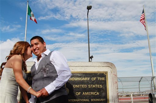 Maricruz Valtierra of Mexico, left, and U.S. citizen Edgar Falcon, right, embrace at the U.S.-Mexico border where they were married, Tuesday, Aug. 27, 2013 in El Paso, Texas. (AP)