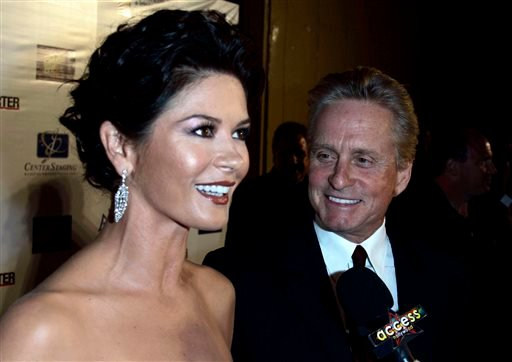 """FILE - In a Oct. 20, 2007 file photo, actors Catherine Zeta-Jones,left, and Michael Douglas are interviewed by members of the media as they arrive at """"A Fine Romance"""" third annual benefit at Sony Pictures in Culver City, Calif. (AP)"""