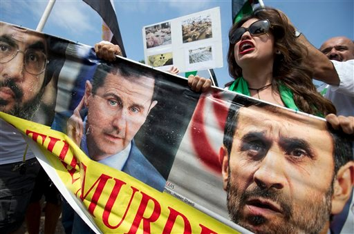 People calling for U.S. military action in Syria, holding a sign with the images of Syrian President Bashar Assad and former Iranian President, Mahmoud Ahmadinejad, shout against others there who do not want military action in Syria.