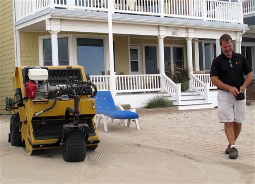 In this Aug. 28, 2013 photo, Marty Sudol pilots a remote-controlled mechanical beach rake that strains debris from sand in front of a home on the Manasquan, N.J. beachfront.