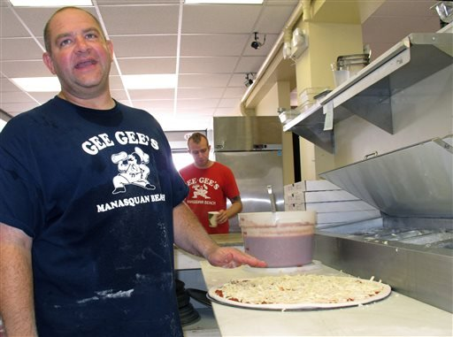 In this Aug. 28, 2013 photo, Matthew Riccelli, general manager of Gee Gee's Pizza on the Manasquan, N.J. beachfront, prepares a pizza. He says business was down in the first summer season after Superstorm Sandy. (AP Photo/Wayne Parry)